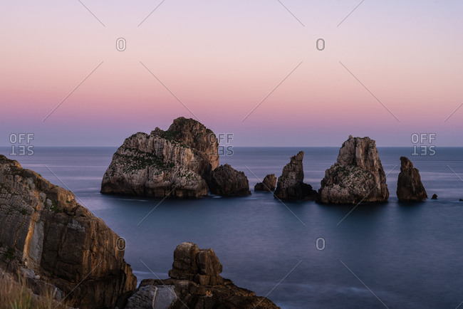 Picturesque scenery of rocks in peaceful sea and skyline in twilight in Costa Brava