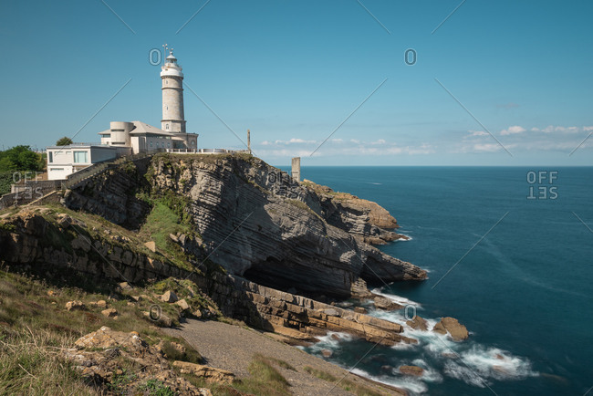 Scenic landscape of white lighthouse on cliff seashore of Costa Brava in sunny day