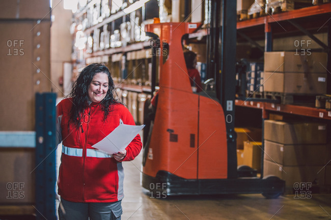 Satisfied black haired woman in red uniform smiling while reading document during work in big storage with packages