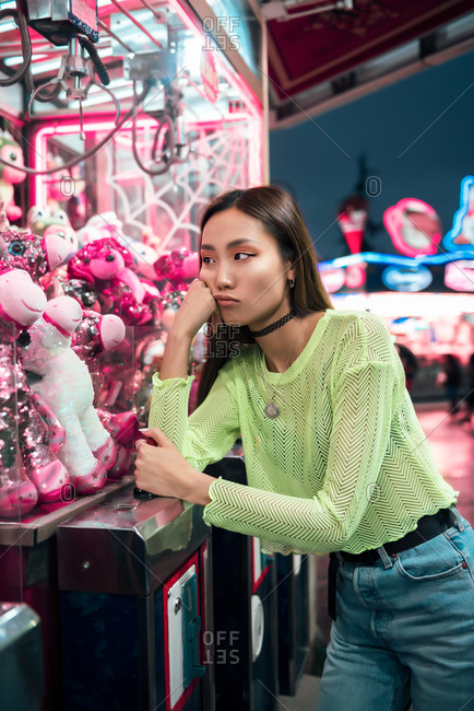 Side view of ethnic alluring woman in stylish clothes touching glass and looking at toys in claw crane machine at night on fairground