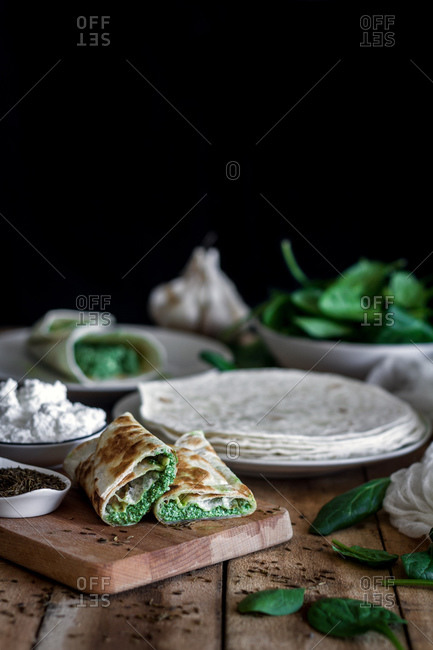From above of tasty tortilla stuffed with puree of spinach on wooden table with ingredients