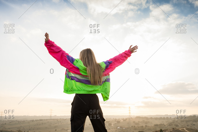 Back view of contemporary blond haired young woman in colorful jacket raising hands with remote land on background