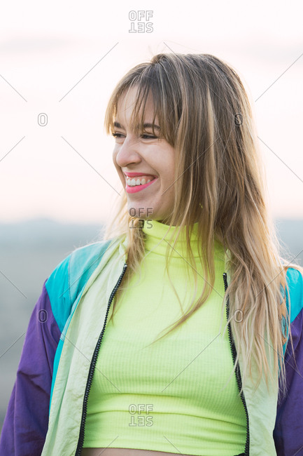Contemporary cheerful blond haired young woman in colorful jacket and green neon top looking away with remote land on background