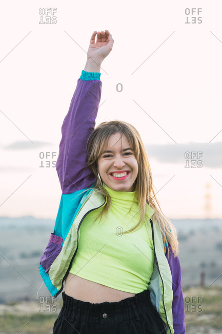 Contemporary cheerful blond haired young woman in colorful jacket and green neon top looking at camera with remote land on background