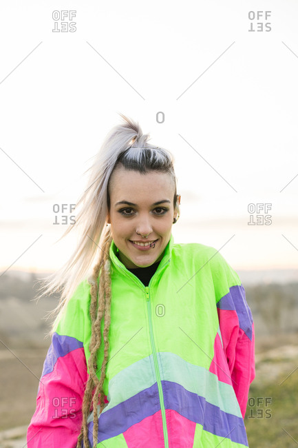 Side view of extraordinary lady with contemporary hairstyle wearing multicolored sportive jacket looking at camera on blurred background of nature