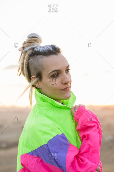 Side view of extraordinary lady with contemporary hairstyle wearing multicolored sportive jacket looking away on blurred background of nature