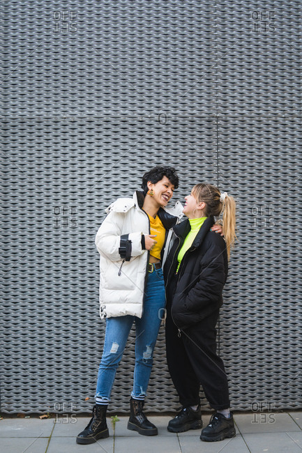 Full length of content cheerful multiethnic female friends in stylish warm clothing standing in embrace and smiling with modern building on background