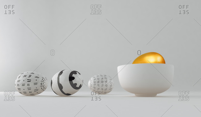 Golden egg on a bowl among painted and decorated Easter eggs on white background