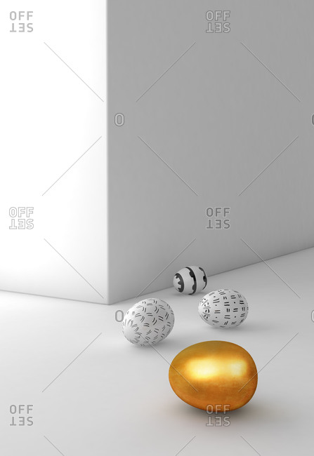 Easter eggs next to a golden egg on white background