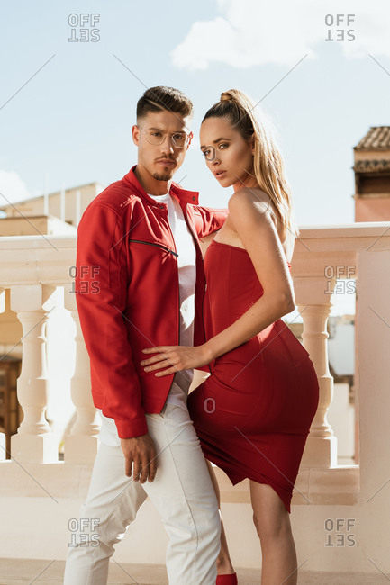 Side view of emotionless male model in stylish red jacket and female model in trendy red dress standing on balcony and looking at camera