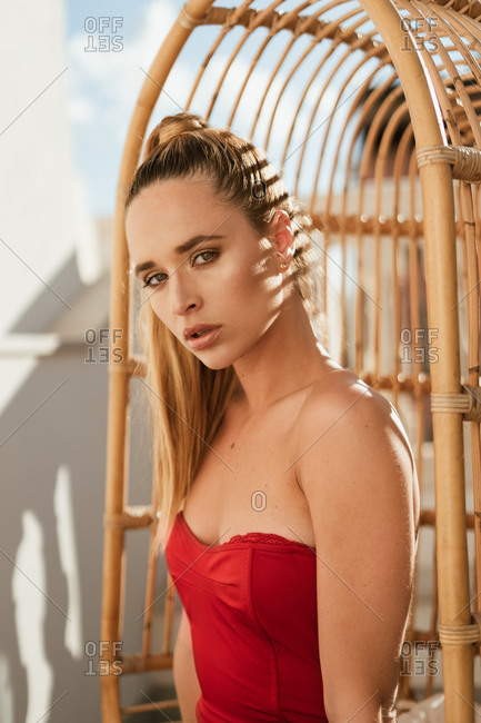 Sensual blonde haired beautiful female model with golden earrings in red stylish dress sitting on hanging chair at outdoors terrace in sunlight