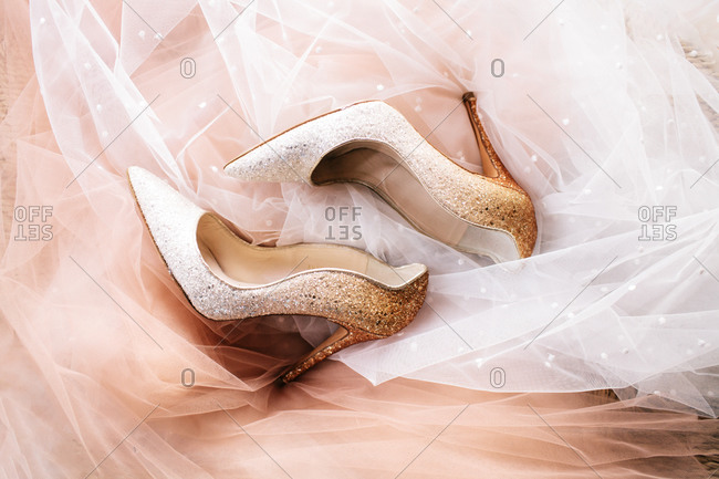 Top view of glittering stiletto shoes placed on pink and white veil fabric with glitters