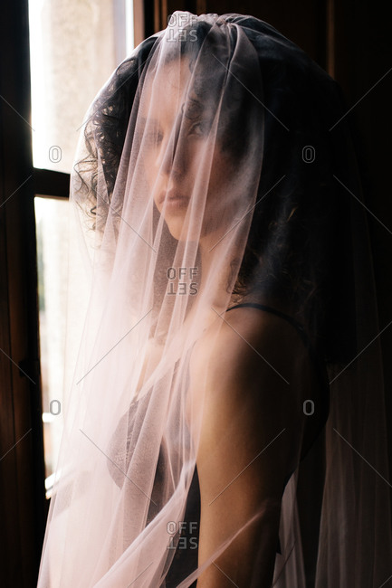 Woman looking at camera with translucent veil standing near window with open shutters in dark retro room
