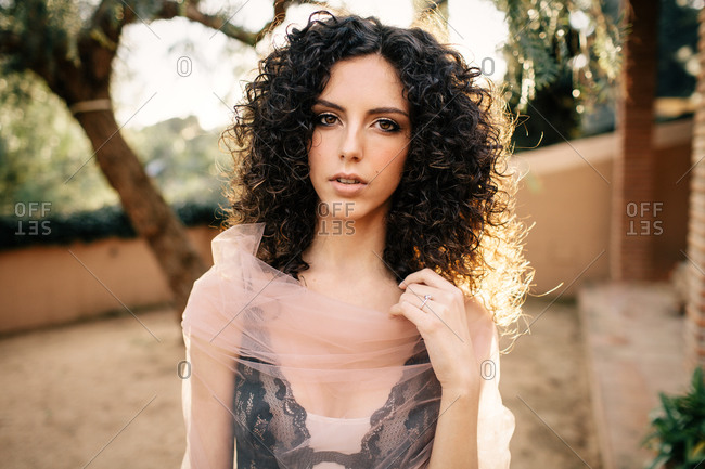 Young beautiful woman in translucent trendy garment standing on path in park looking at camera