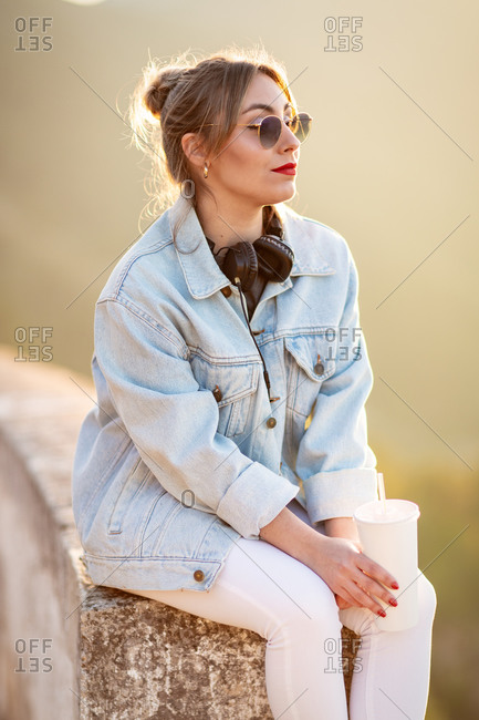 Side view of young woman in casual wear with sunglasses resting on rocky fence with beverage and listening music with headphones