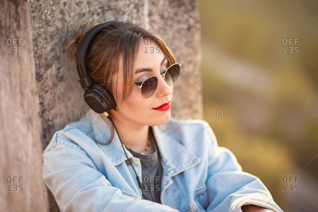Joyful young woman with sunglasses in trendy casual outfit smiling and looking away on sunny day