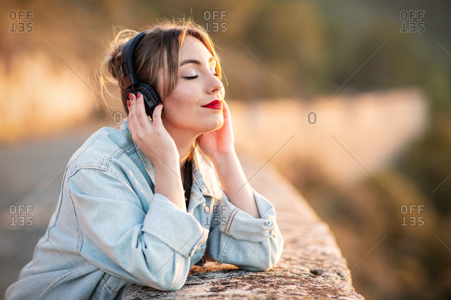 Side view of satisfied young lady in stylish casual wear and red lips leaning elbow on rocky fence with closed eyes while listening music with headphones