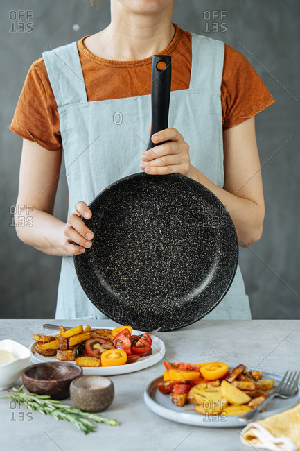 Unrecognizable female with empty frying pan standing near table with delicious roasted vegetables in kitchen