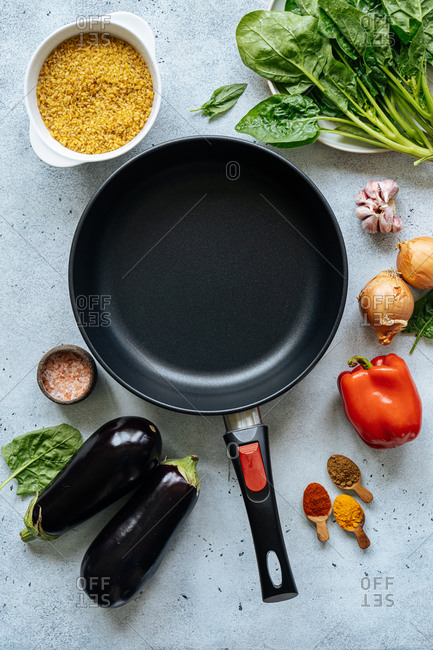 From above various vegetables and spices for lunch preparation arranged around empty frying pan on table in kitchen