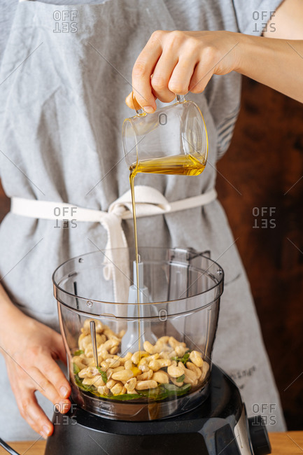 Unrecognizable woman adding oil to cashew while preparing healthy vegan dish in blender at home