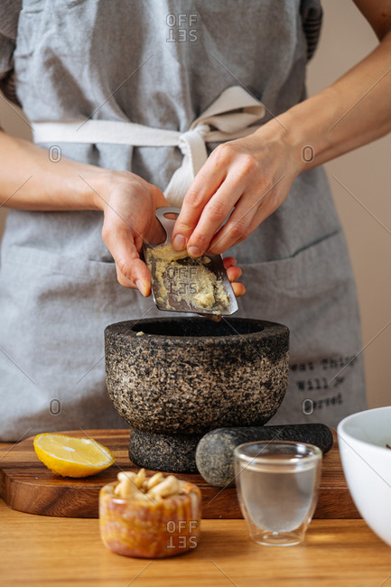 Unrecognizable female in apron grinding fresh ginger into mortar while preparing healthy dish in kitchen at home