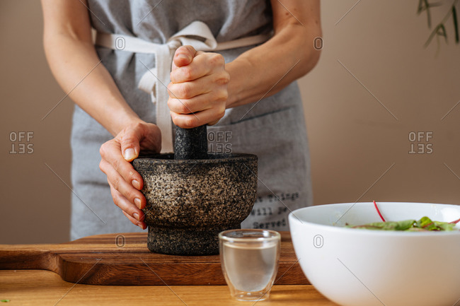 Anonymous lady in apron using mortar and pestle to crush ingredients for sauce while preparing healthy salad at home