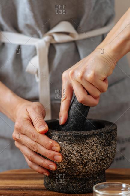 Cropped woman crushing ingredients in mortar