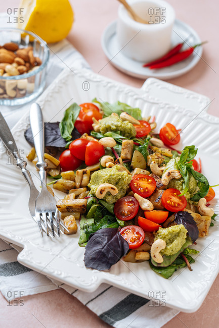 Appetizing colorful healthy fresh salad with vegetables and cashew nuts garnished with basil leaves served on white plate with forks