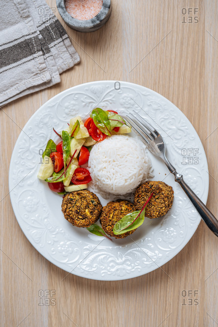 Top view of white plate with vegan cutlets served with white rice and fresh vegetable salad on wooden table