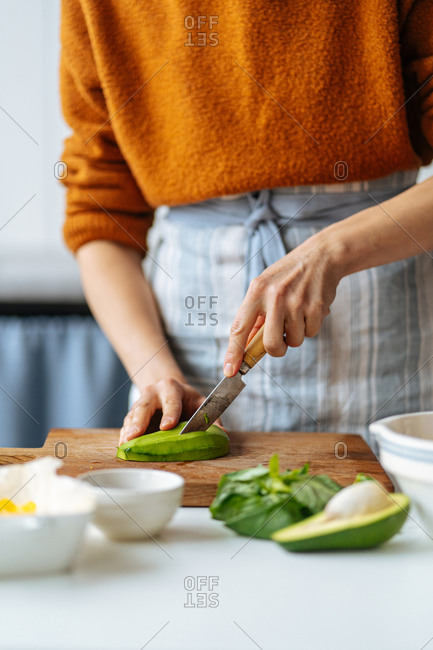 Woman cutting avocado on cutting board