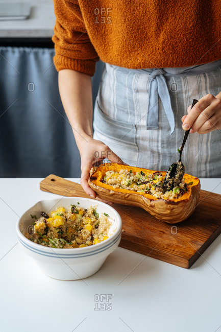 Cropped housewife filling baked butternut pumpkin with vegetarian mix of quinoa and vegetables at white table in home kitchen
