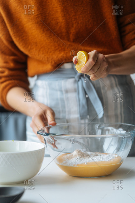 Glass bowl with orange vegetable mixture in hands of Cropped cook squeezing ripe lemon into puree at table