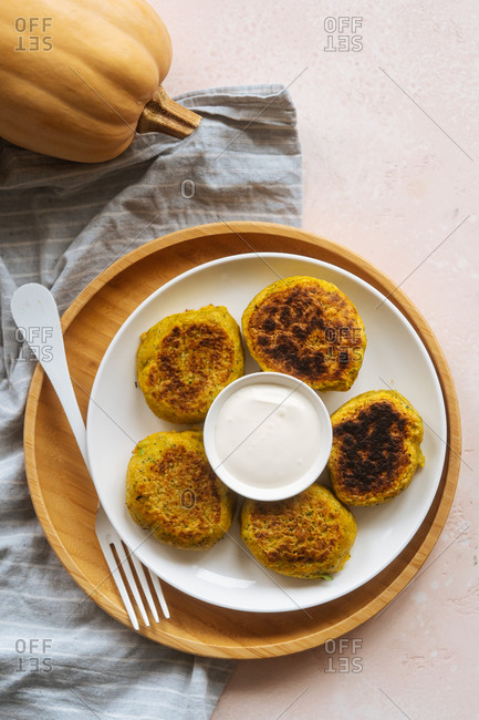 From above fried tasty appetizing cutlets in white plate with sour cream on served table with pumpkin and linen