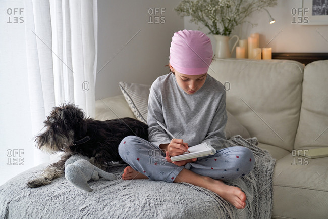 From below happy little child with cancer disease writing notes while sitting with dog on bed in room