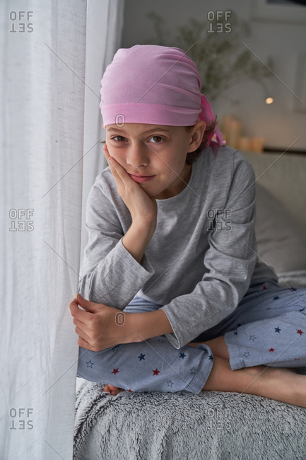 Serious cute child in pink bandana looking at camera and fighting cancer at home sitting in a couch
