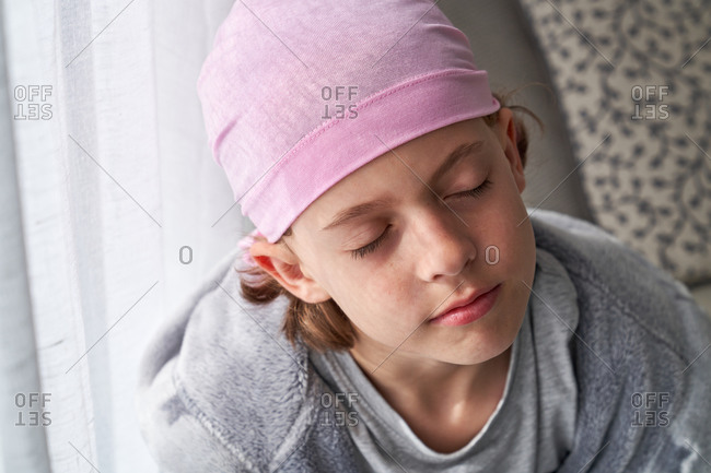 Serious cute child in pink bandana with closed eyes fighting cancer at home sitting in a couch