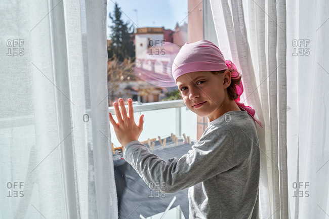 Side view of kid with cancer wearing pink bandana and putting hands on window in room looking at camera