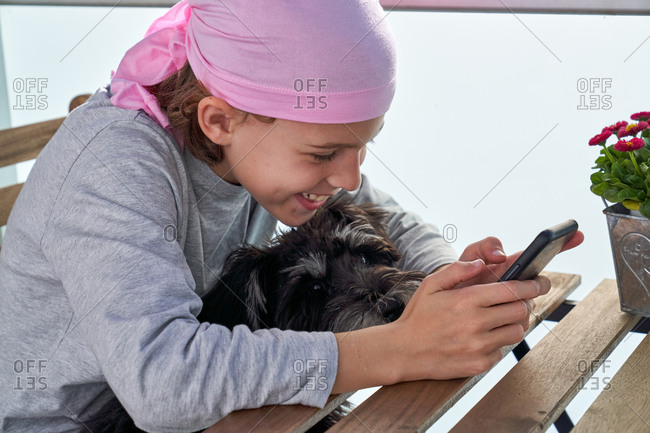 Cheerful little child with cancer disease enjoying pastime with cellphone on terrace while holding a small dog