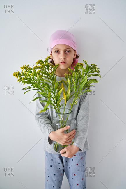 Focused little boy with cancer diagnosis wearing pink bandana and looking at camera while holding vase with flowers and standing at wall
