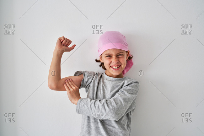 Brave small child with cancer diagnosis looking at camera and screaming while raising fists up on gray background