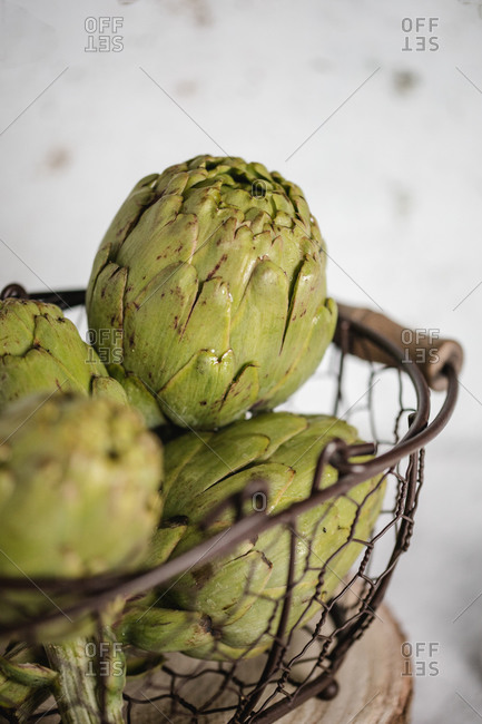 Bright green artichokes in metal stylish basket decorated with green leaves on table