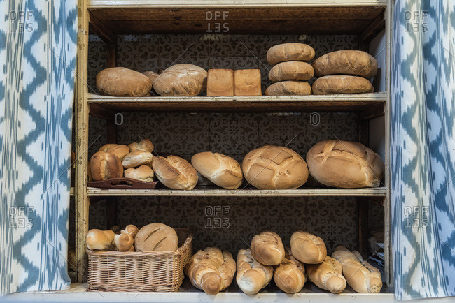 Loaves of assorted fresh bread for sale placed on shabby shelves near curtains in bakery