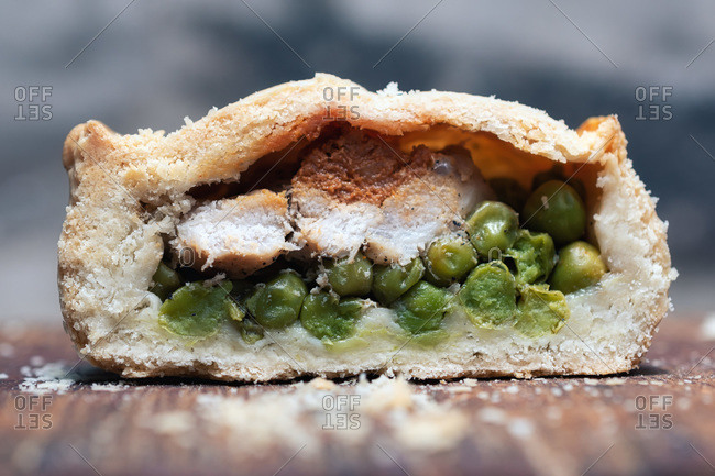 Closeup half of cut small pie with yummy meat and peas placed on table in bakery