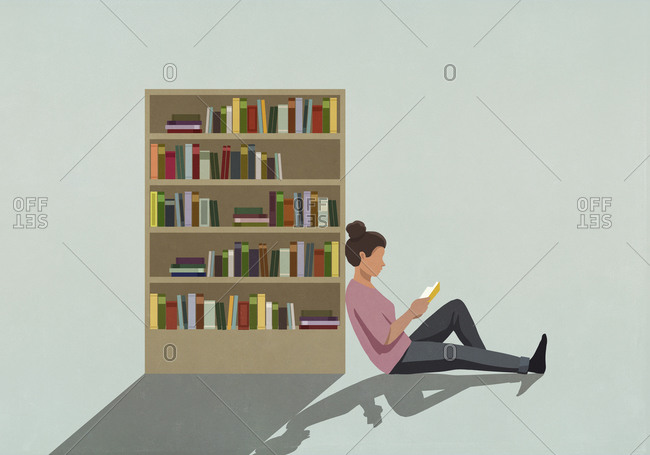 Woman reading book against bookcase