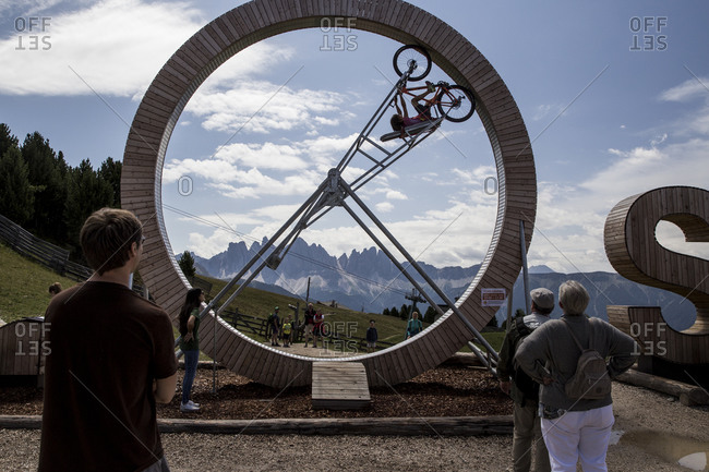 July 21, 2017: People watch as a woman rides a mountain bike upside down in a wheel at the ski resort of Plose in the South Tyrol region of Italy.