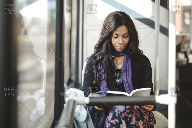 African American woman reading a book by the bus window