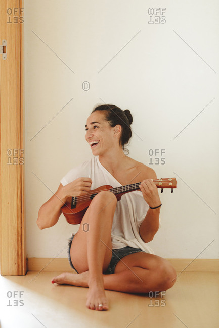 Woman sitting on the floor of the house playing the ukulele and laughing, as she looks to the side