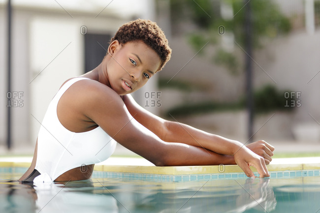 Young and sexy afro american woman with short hair, looking at the camera while posing wearing a swimsuit inside the pool.