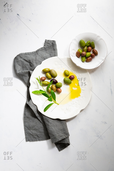 Pickled green and black olives on white plate