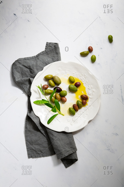 Overhead view of pickled green and black olives on white plate